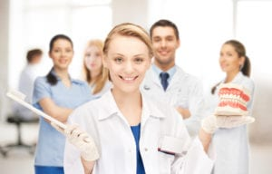female dentist with smiling team standing behind her